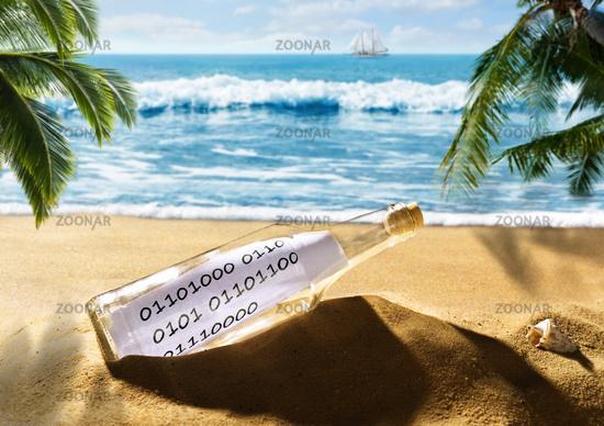 Flaschenpost mit einer Nachricht in Binärcode am Strand