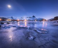 Frozen sea coast, beautiful snow covered mountains and starry sky