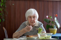Solitary senior woman eating her lunch at retirement home.