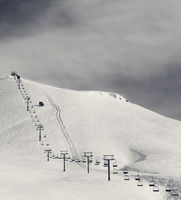 Black and white view on ski slope and chair-lift at morning