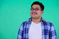 Face of happy young overweight Asian hipster man thinking