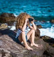 Little girl looking far away with binoculars