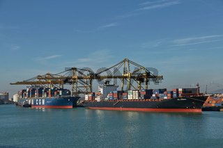 Port crane loads a container on Pier for transportation of import export and business logistic in Barcelona Spain.