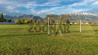Panorama frame White soccer goal on a grassy sports field with view of snow topped mountain