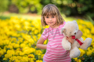 Adorable little girl with a white teddy bear