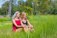 Two young women sit together in nature