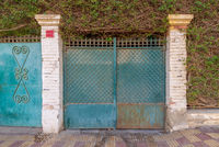 Background of green old weathered grunge antique wrought iron gate with geometrical pattern ornaments and two white bricks columns