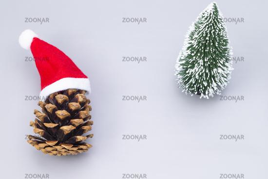 Tannenzapfen mit roter Mütze und Tannenbaum
