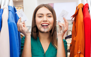 happy woman with price tags at clothing store