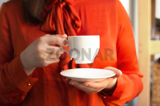 Business lady drinking coffee in office.