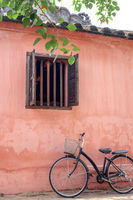 Old bicycle parked near house wall with window