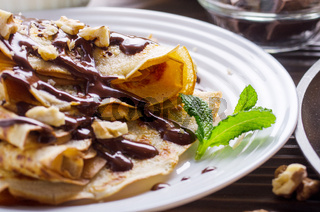 French crepes with chocolate sauce and walnuts in ceramic dish on wooden kitchen table
