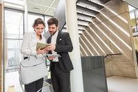 Geschäftsleute schauen gemeinsam auf Tablet