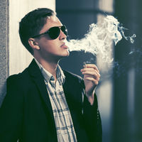 Young handsome man in sunglasses smoking a cigarette in city street
