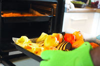 Close up shot of roast pepper and eggplant in a tray. A man is holding it in his hands wearing oven gloves