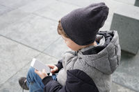 7 year old boy looking at smartphone outdoors in winter