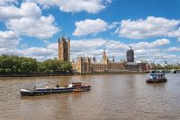 Passenger ships and service boats in front of Parliament of London, UK, on a bright day.