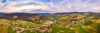 Aerial drone view of urban village Pidbuzh in Carpathians, Ukraine. 180 degrees panoramic landscape of countryside. Sunset time, end of summer