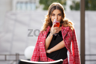 Young fashion woman in red tweed jacket and skirt suit at sidewalk cafe