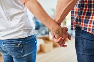 Paar hält sich an den Händen beim Umzug