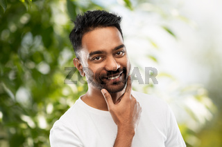 smiling indian man touching his beard