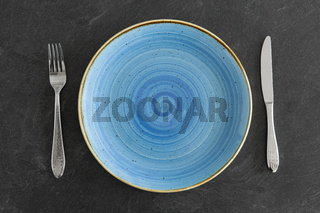 close up of plate, fork and knife on table