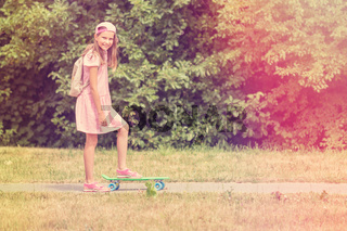 Little girl with skateboard in a park
