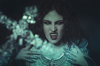 fear of the cross vampire, demonic woman dressed in white lace and silver jewelry. has fangs and thick brown hair