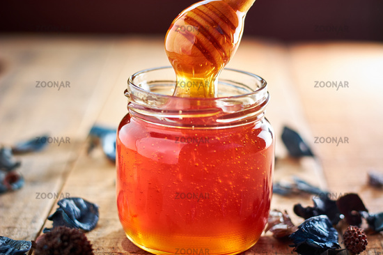 Glass jar full with honey and wooden spoon