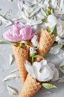 Card for congratulations of wafer cones with gentle white and pink flowers peony, petals on a gray stone background.