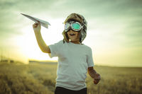 boy at sunset playing at being aviator, he wears pilot glasses of airplanes and some cardboard like wings