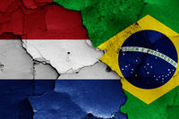 flags of Netherlands and Brazil painted on cracked wall