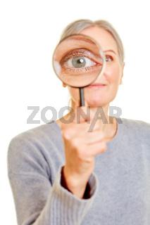 Alte Frau hält Lupe vor ihr Auge