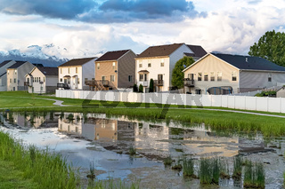 Homes and cloudy sky reflected on the shiny surface of a grassy pond