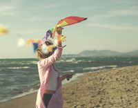 Young Woman holding kite at beach on autumn day