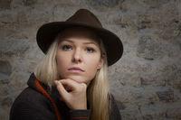Nachdenkliche junge Frau mit braunem Hut
