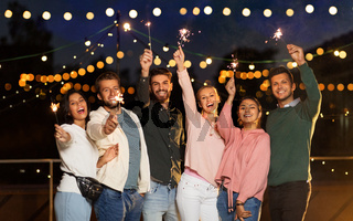 happy friends with sparklers at rooftop party