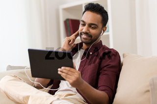 man in earphones with tablet pc listening to music