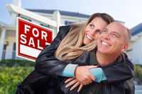 Happy Couple Hugging in Front of For Sale Real Estate Sign and House