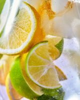 Macro citrus drink background with lemon and lime slices in a glass.