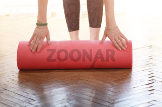 Female hands unrolling yoga mat before workout exercise. Healthy lifestyle concept