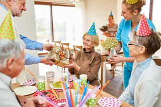 Senior Frau erhält Geschenk auf Geburtstagsfeier