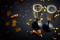 Two glasses full of sparkling champagne wine with golden decoration
