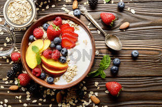 Flat lay of fruit healthy muesli with peaches strawberry almonds and blackberry in clay dish with yogurt