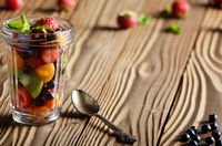 Assorted berries in mason jar on kitchen wooden table with spoon aside