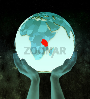 Tanzania on blue globe in hands