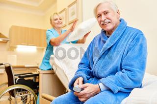 Senior Mann sitzt auf seinem Pflegebett