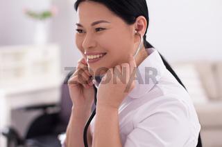 Nurse using stethoscope on patient.
