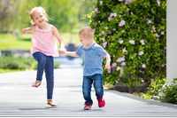 Young Sister and Brother Holding Hands And Running At The Park