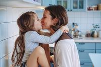 Mom kisses her little daughter in the kitchen